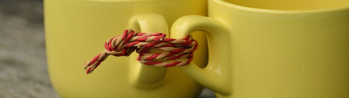 two yellow cups tight together with red rope