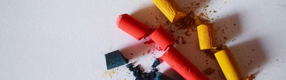 broken colour chalks on white paper