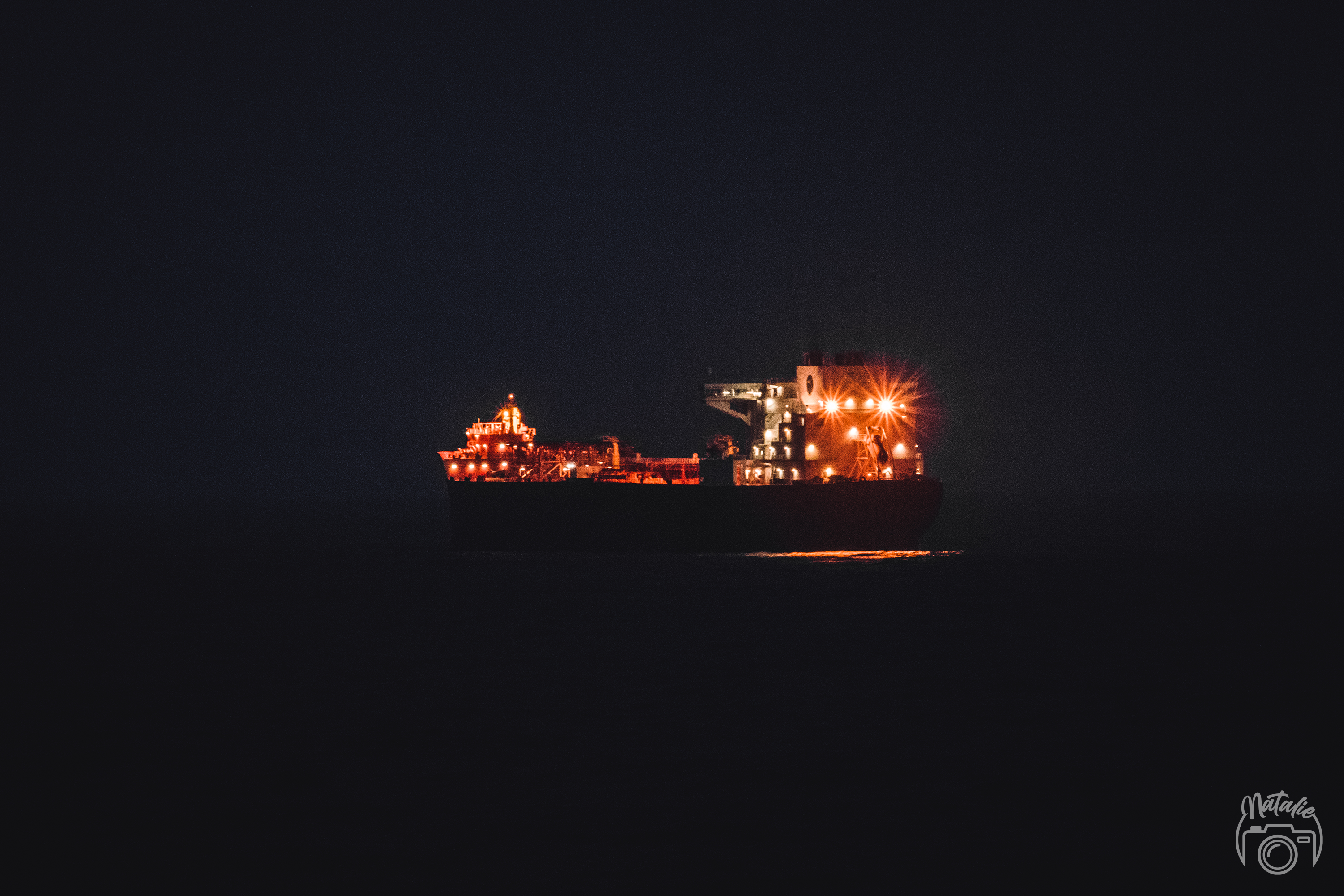 Transporting ship with glowing lights in pitch-black night on the ocean