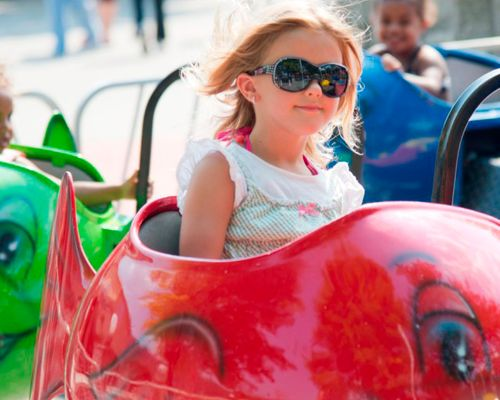 Little girl with sunglasses riding the Whales Kiddie Ride at DelGrosso's Amusement Park