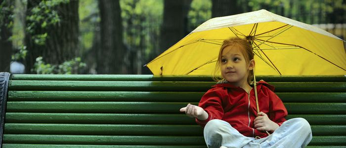 Girl sitting on bench with umbrella