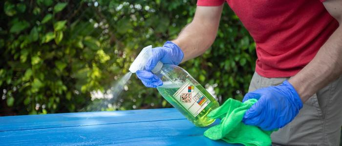 Man spraying cleaner on a table