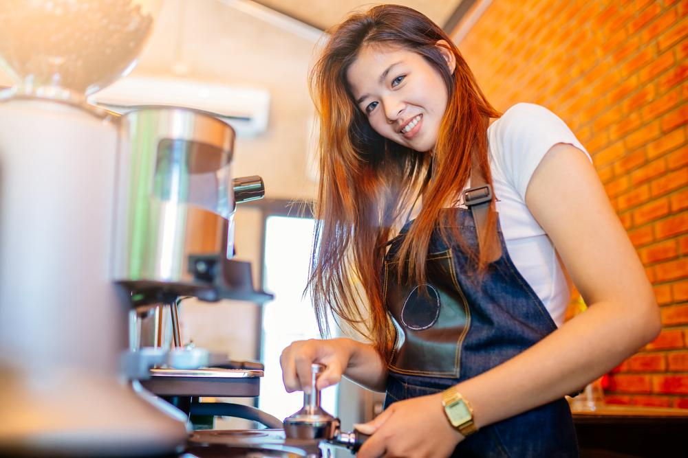 A  Barista wearing an apron to make coffees.