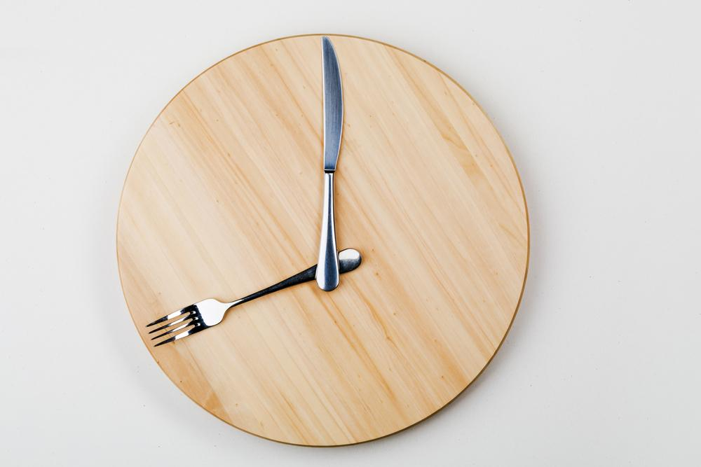 A wooden clock with the hour hand as a fork and minute hand as a knife.
