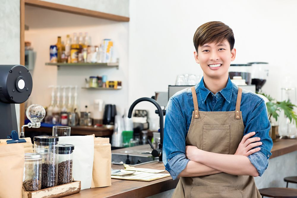 A smiling confident barista who is serving in a cafe.