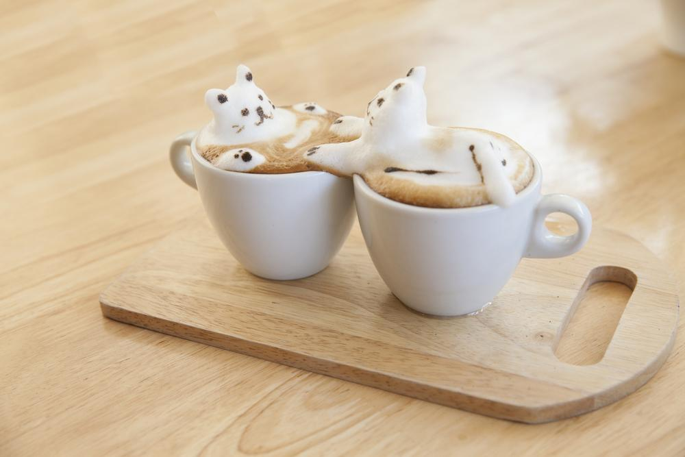 A coffee art design that features a bear between two coffee cups.