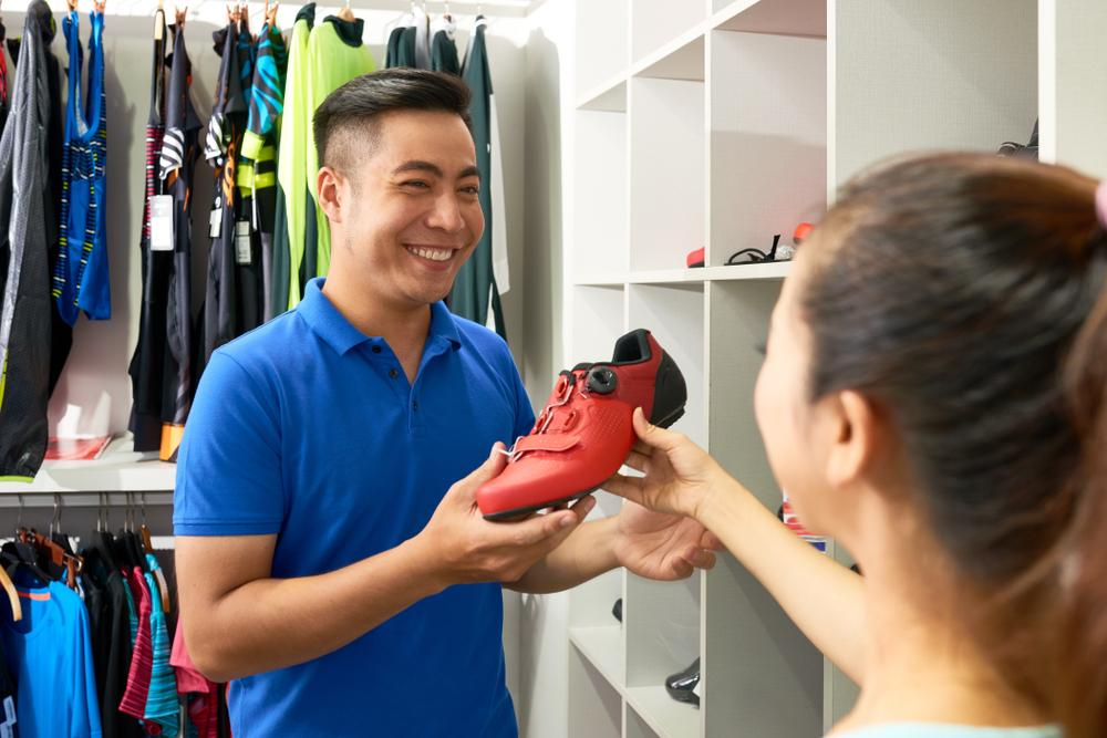 A sales executive selling shoes to a customer.