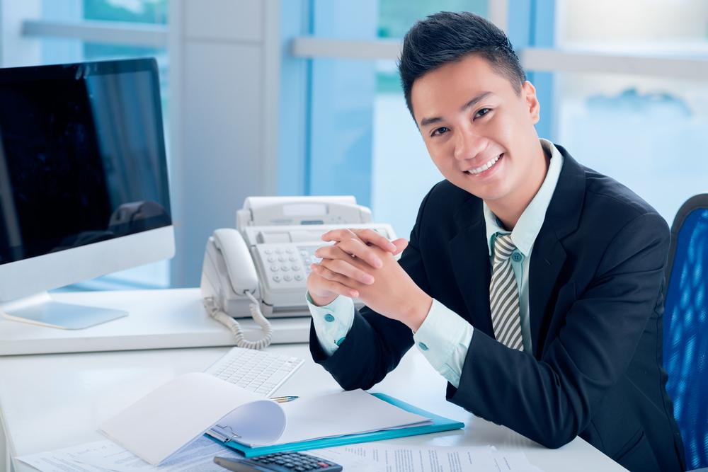 A financial advisor smiling in his office.