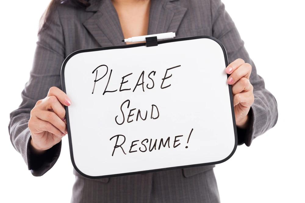 """A Businesswomen holding a small whiteboard with the words """"please send resume!"""" written on it."""