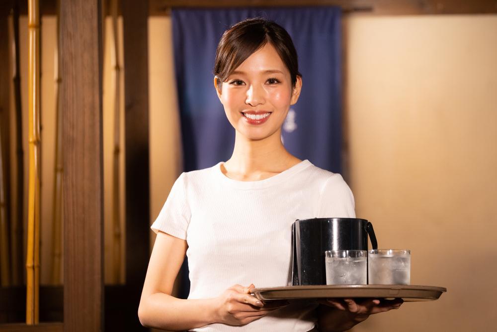 A restaurant service crew doing her waitering job.