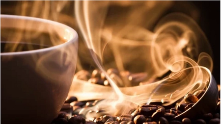 steaming coffee cup surrounded by coffee beans