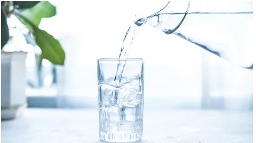 a pitcher of water pouring water into a clear glass filled with ice