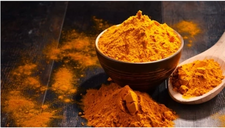Orange curry powder in a dark bowl and scattered on the table