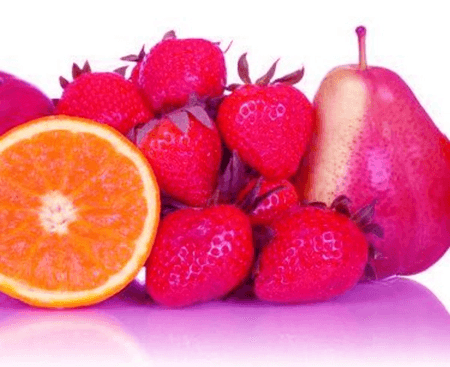 Strawberries, a pear, and a orange laying side-by-side against each other