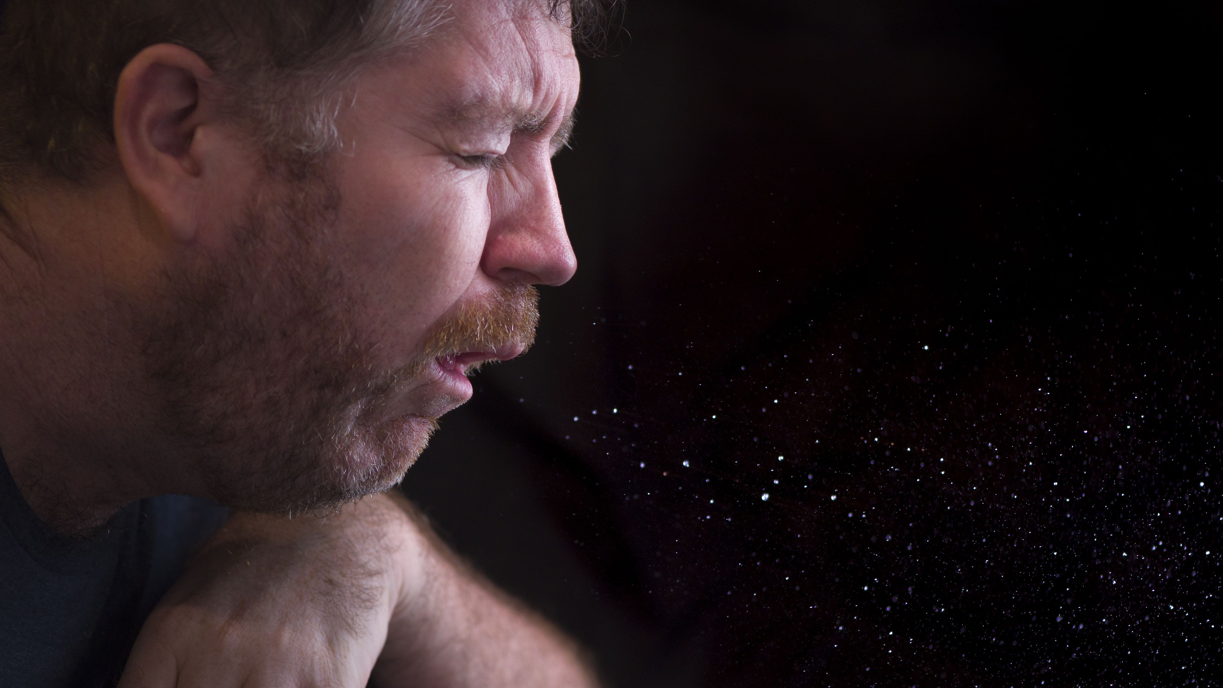 Man sneezing particles in the air