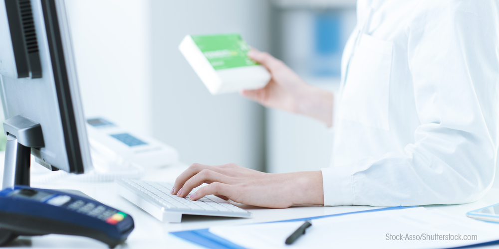 Pharmacist entering information into computer