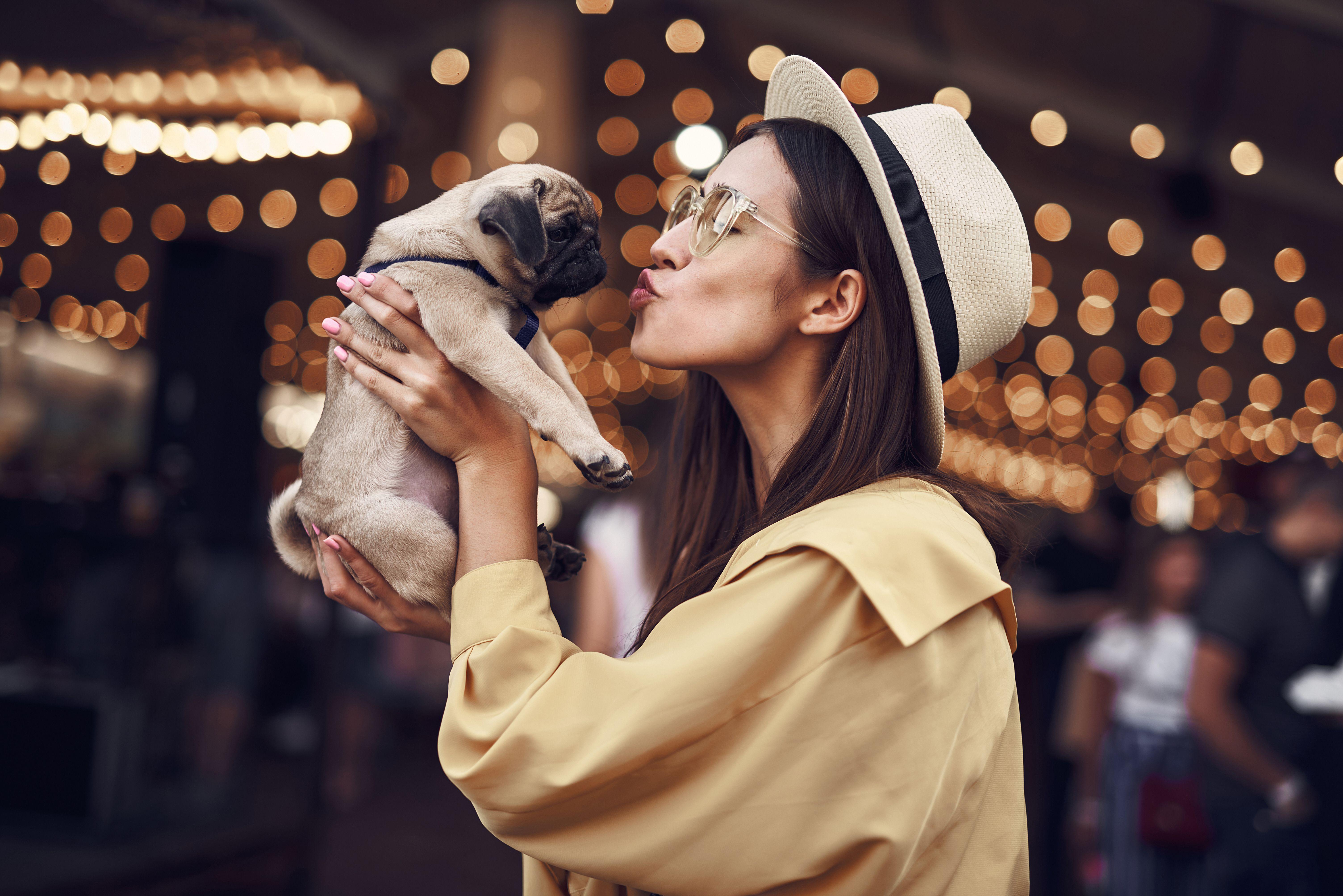young woman kissing bulldog puppy