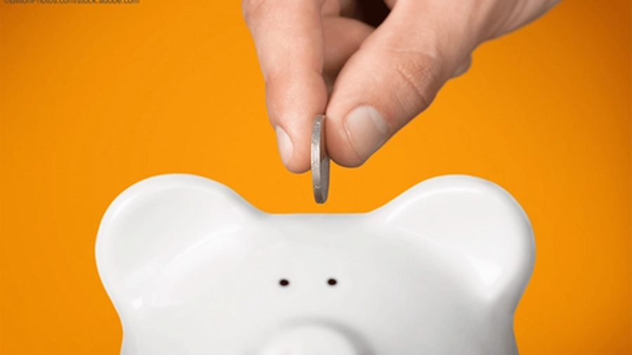 hand placing coin in white piggy bank