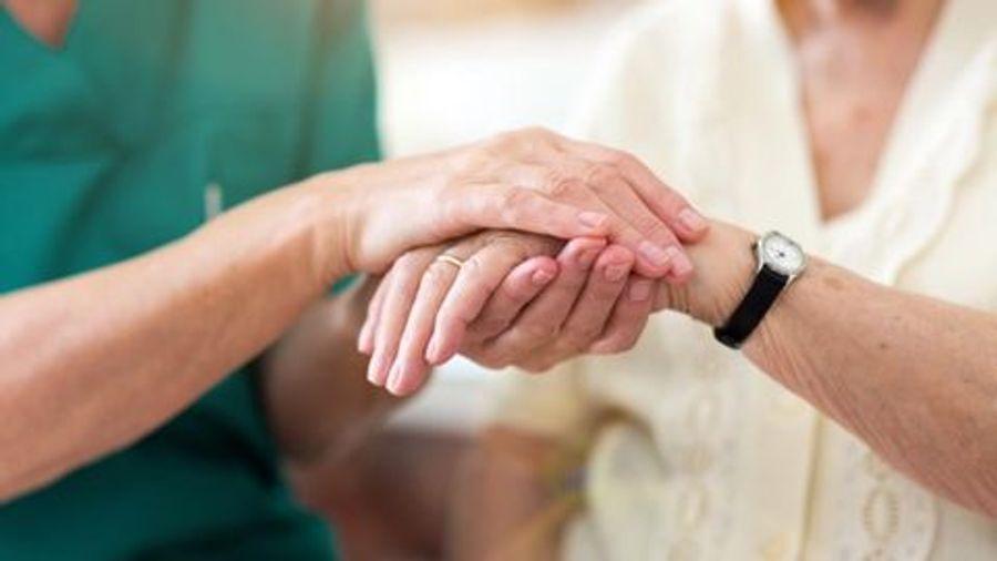doctor holding elderly patient's hand
