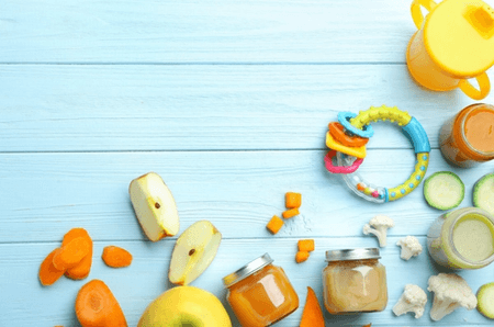 baby food and toys on a baby blue colored table