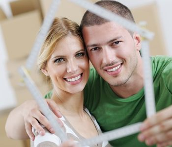 Couple holding a house model.