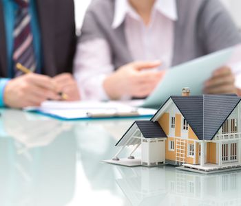 Signing VA loan offer with a house concept in table.