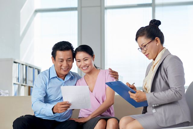 Asian couple going over MRP certification with VA Loan specialist.