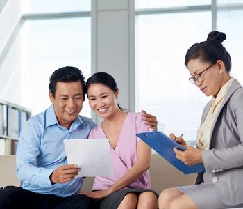 Asian couple going over MRP certification with VA Loan specialist