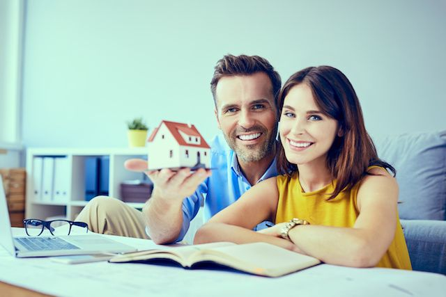 Couple holding house model and reading documents.