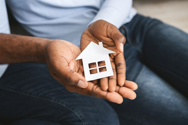 Hands holding a small house model.