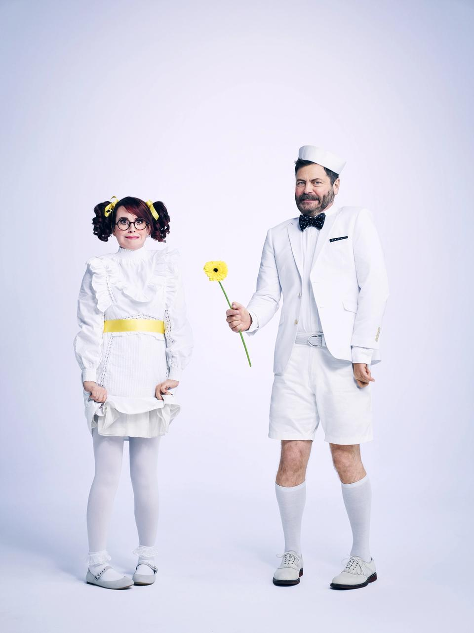 Megan & Nick dresses up as young children in all white clothing. Both looking awkward. Nick holding a yellow flower.