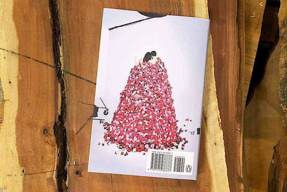 Greatest Love Story face down on a slab of wood showing rear cover with Nick & Megan underneath many roses.