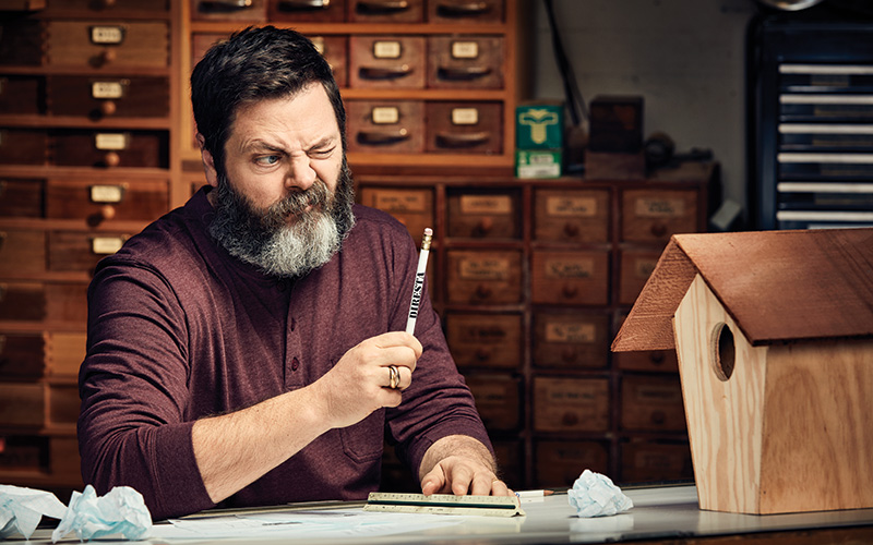 Nick Offerman sitting at a desk with pencil and ruler in hand, staring at a wooden birdhouse.