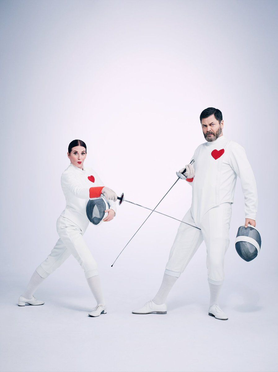 Megan Mullally & Nick Offerman in fencing attire with red heart badges. Megan is poking Nick in the groin with her sword.