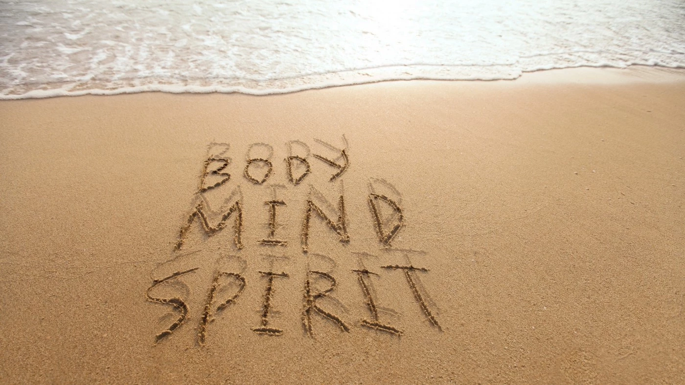 Body, mind, and spirit drawn into the sand with the ocean shoreline at the top.