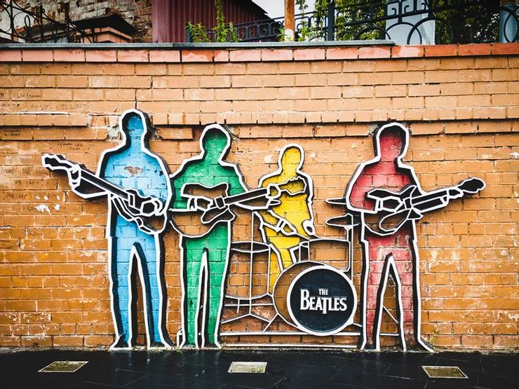 A painted mural on a brick wall of The Beatles in abstract form in bright colours.