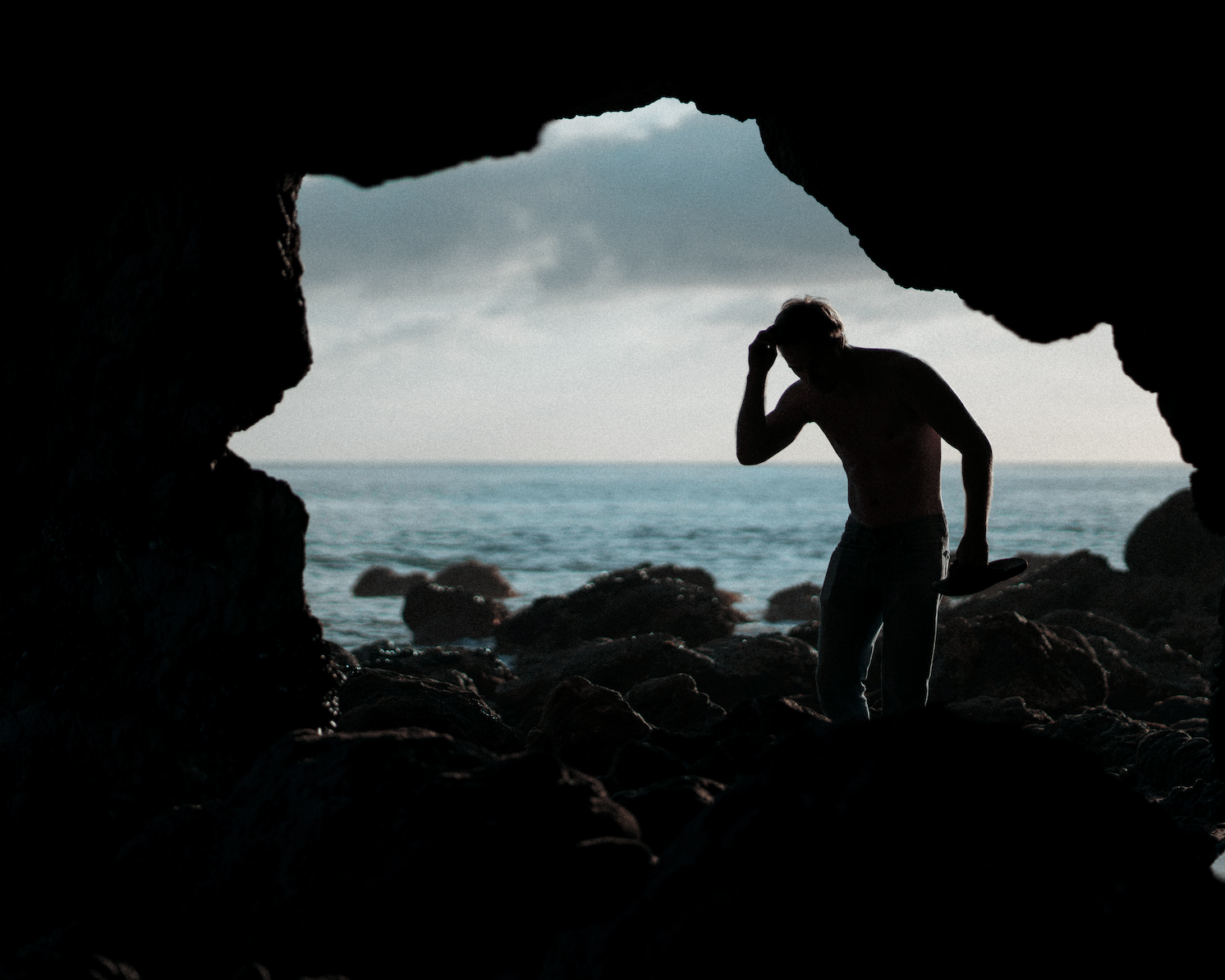 A back-lit shot out of a cave, ocean in the background, with a man scratching his head.