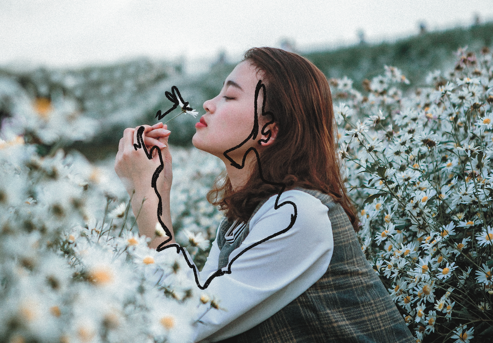 A woman crouches in a flower field smelling a daisy with her eyes closed.