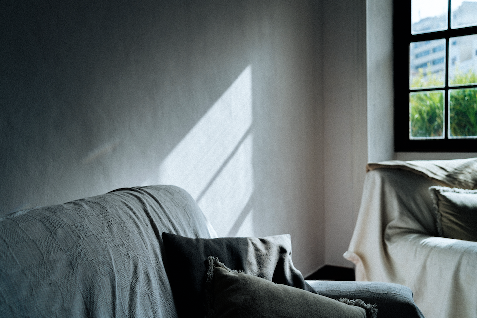 A corner of a grey living room with two couches and sunlight streaming in through a window.