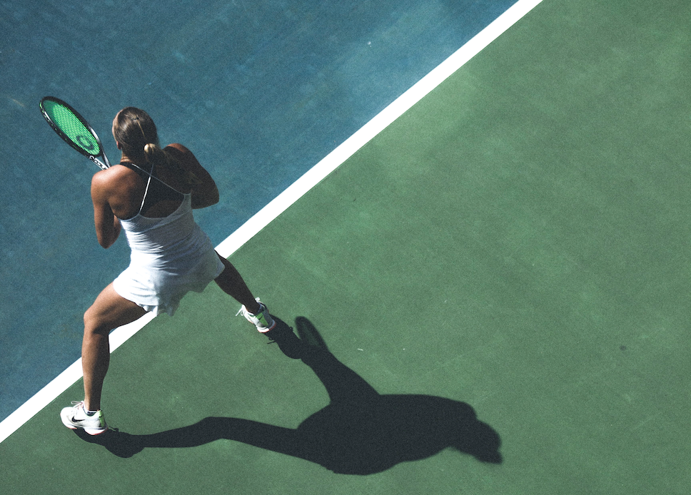 An aerial view of a woman holding a tennis racket on a court.