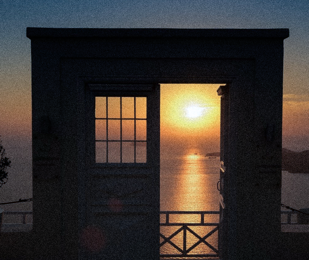 A doorway opens up to a sunsetting over the ocean.