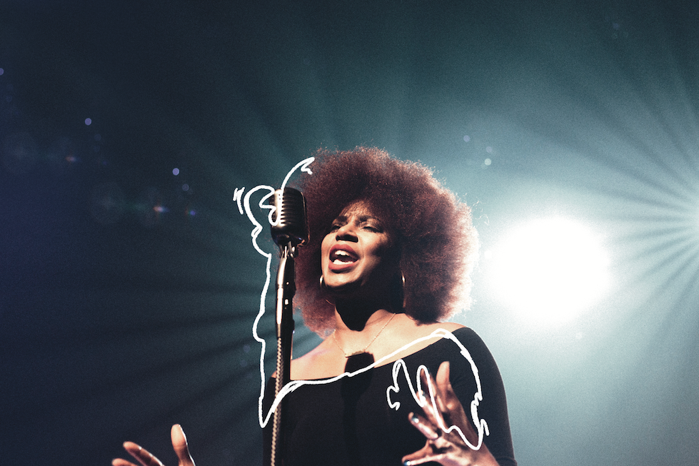 A woman sings on stage with a microphone, and bright stage lights behind her.