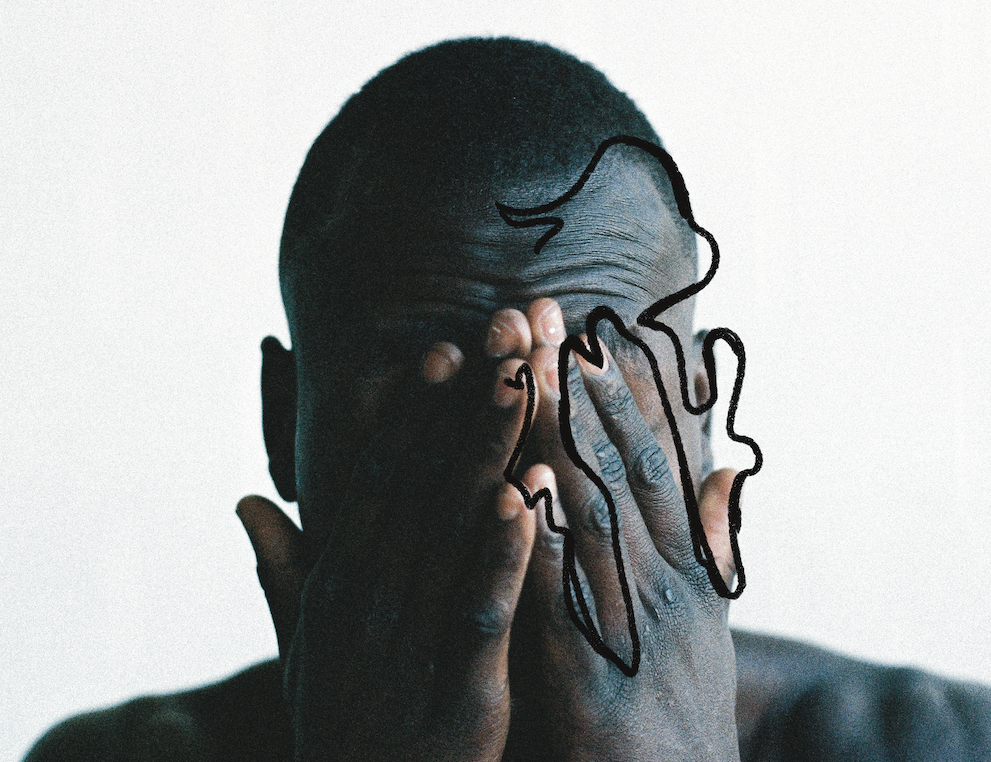 A close up of a man covering his face with his hands.