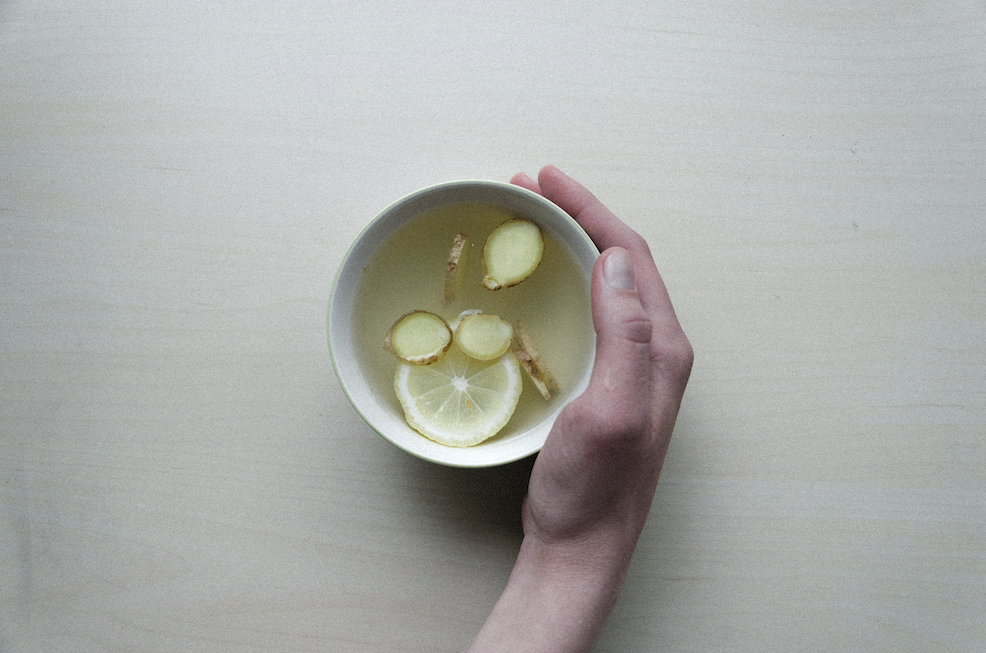 An aerial view of a hand holding a hot cup of lemon and ginger tea.