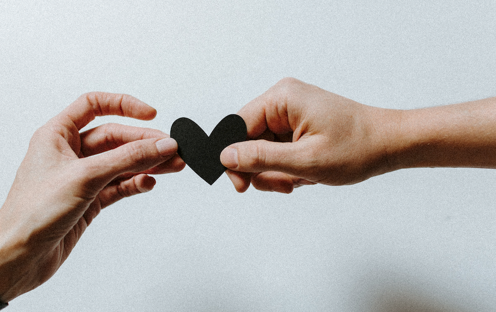 A close up of two hands, with one handing the other a black paper heart.