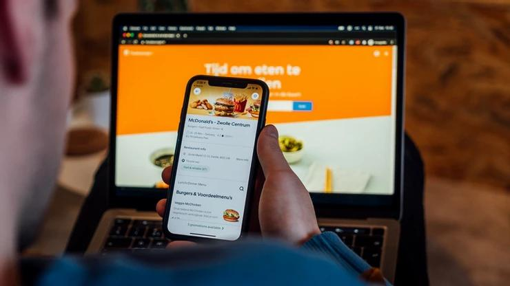 An over-the-shoulder shot of a man on his phone, laptop on his lap, on a food delivery service app.