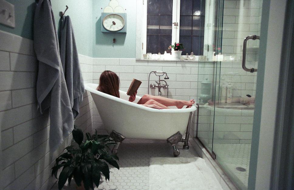 A woman sits in a bathtub, reading a book.