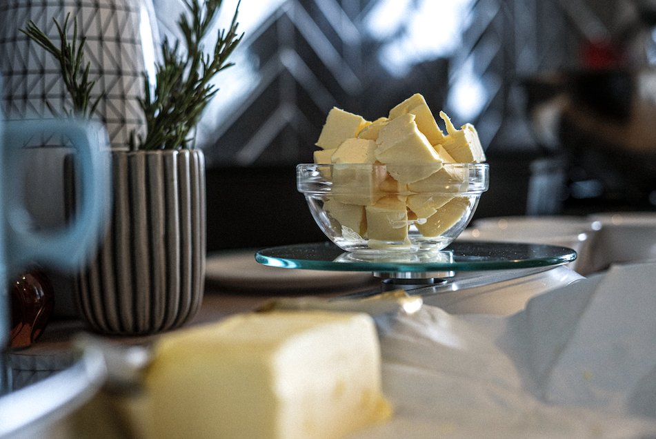 A clear bowl of cubed butter sits on a kitchen table. Another block of butter is blurry in the foreground.