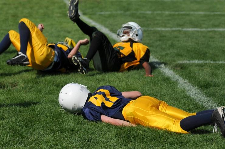 Three young football players lay in the field.