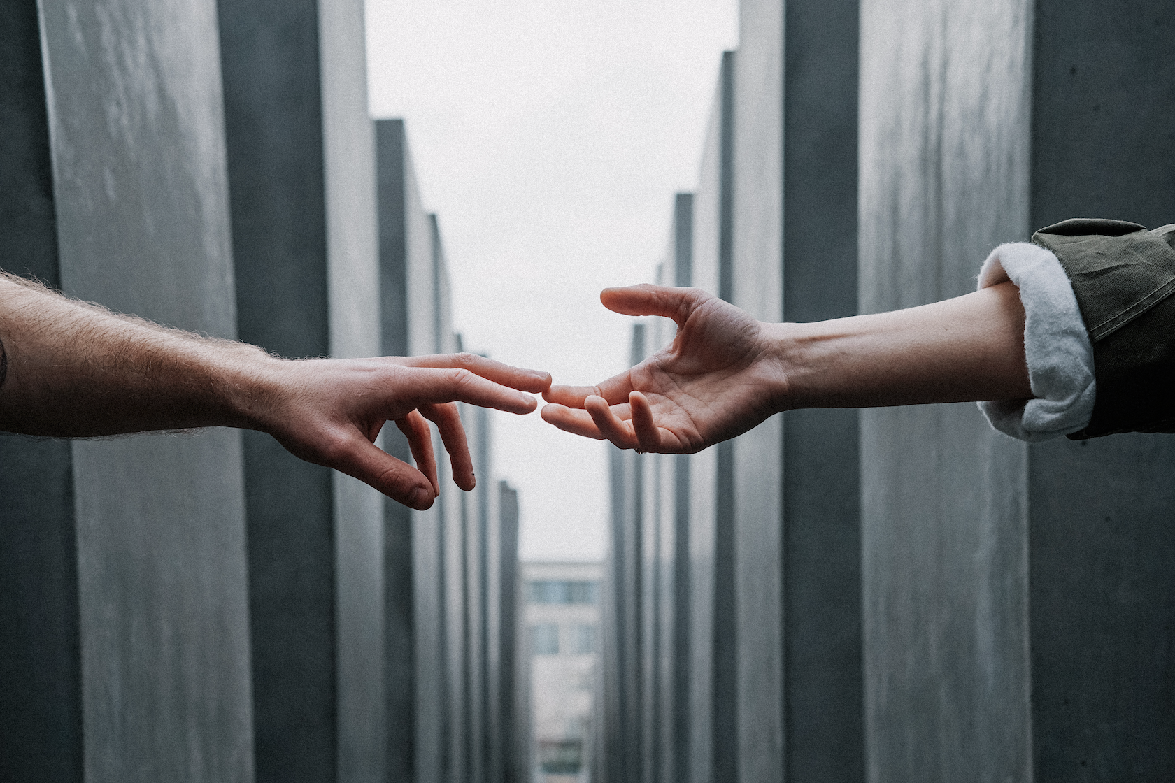 Two hands reach out to each other with buildings in the background.